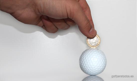 Imagen de una bola de golf y una mano con un euro