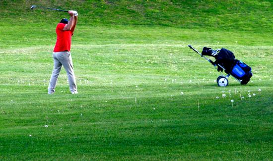 Imagen de un golfista en medio de un pradera haciendo un swing de golf