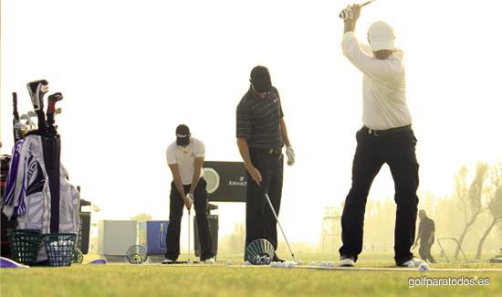 Imagen de tres jugadores de golf profesionales entrenado el swing en el campo de tiro largo