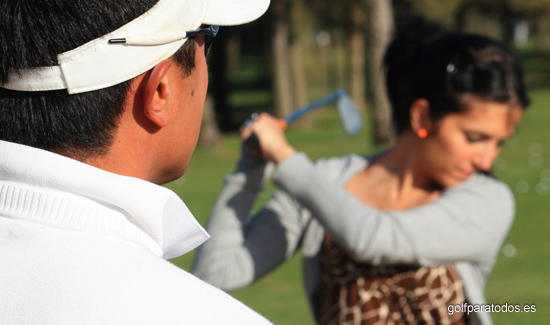 Imagen de un profesor de golf dando clase a una alumna